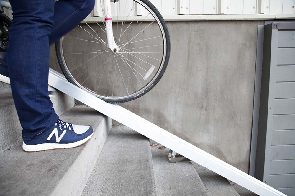 Cyclist walking down stairs with bike