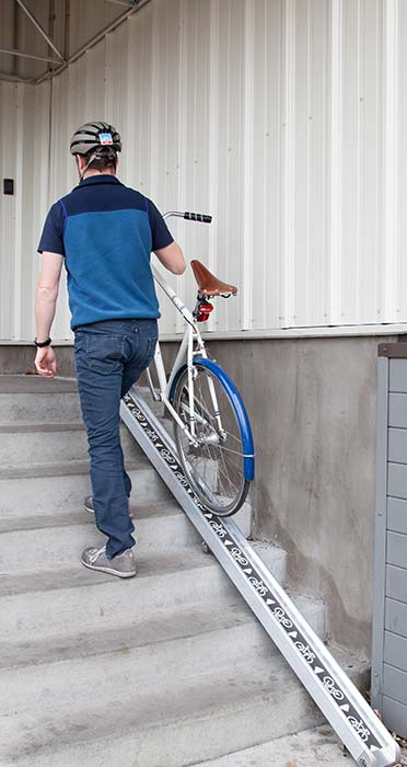 Cyclist walking up stairs with bike