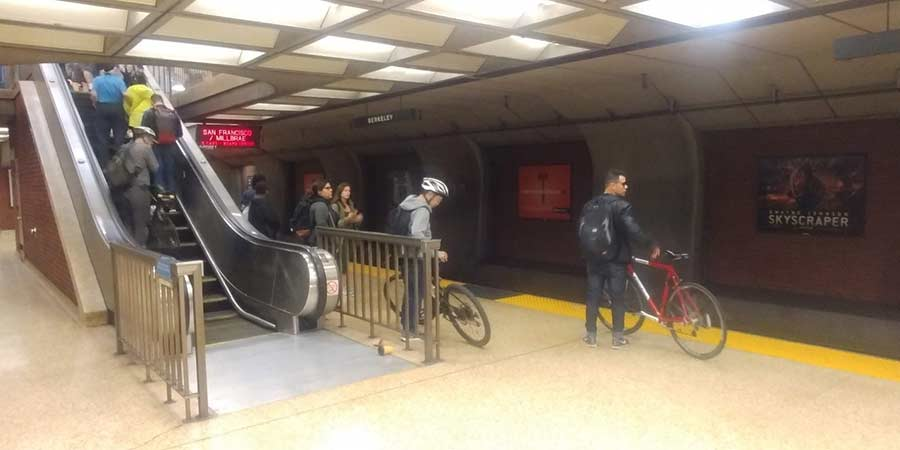Commuters wait with bikes in tow for the next BART train
